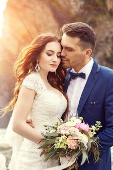 日没で抱き締めるカップル、日没でキスする恋人のカップル。屋外での結婚式