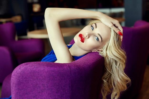 椅子に座っている青いドレスのファッション若いブロンドの女性