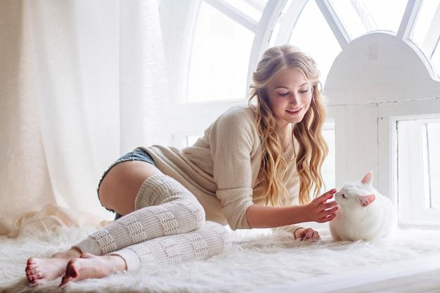 猫と一緒に窓に座って美しいセクシーなブロンド