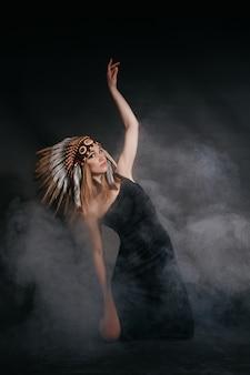 Идеальная женщина в одежде американских индейцев в дыму на сером