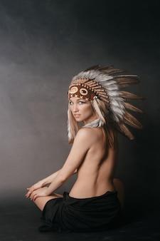 Обнаженная идеальная женщина в одежде американских индейцев в дыму на сером