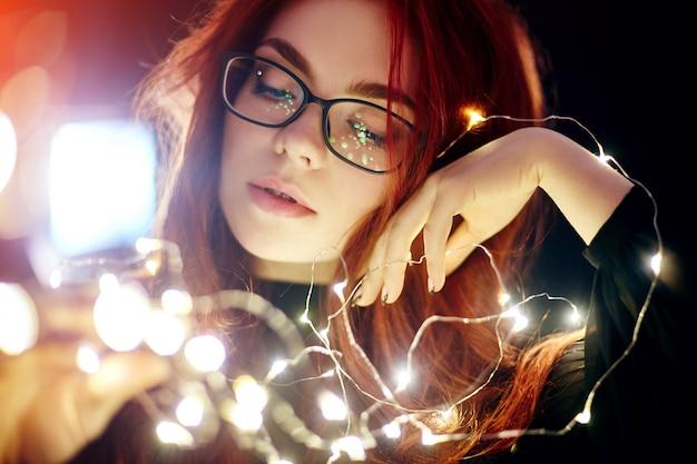 クリスマスライトの赤い髪を持つ女性の芸術の肖像画。
