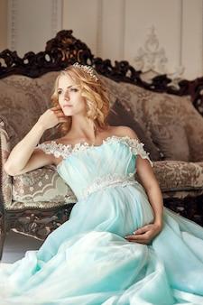 ウェディングドレスの高級ファッション妊娠中のブロンドの女性。