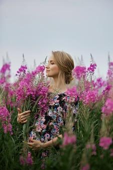 妊娠中の女性が花火草のフィールドを歩いて