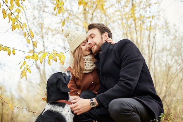 公園で犬と一緒に歩くカップル