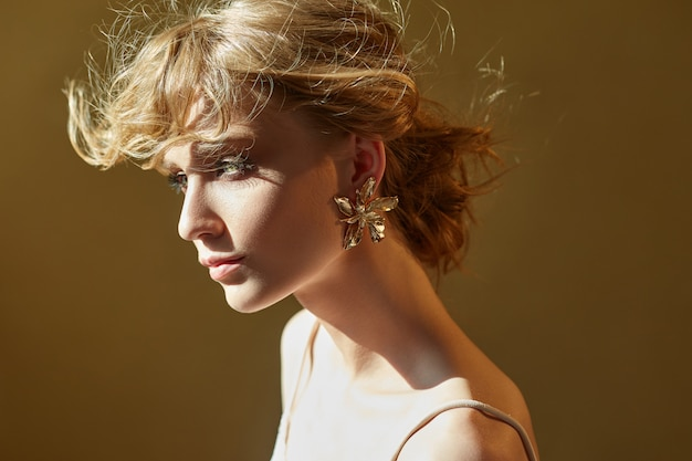 宝石で飾られたイヤリングを持つ美しい女性