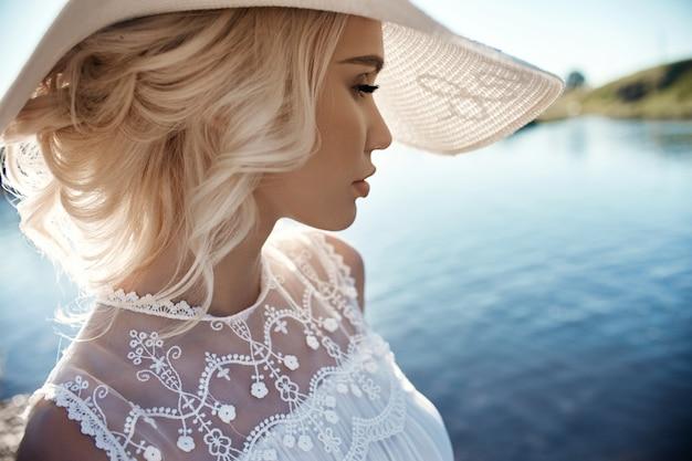 大きな白い帽子の女は海のそばに立つ