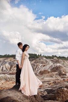 Влюбленная пара обнимает на фоне красных гор.