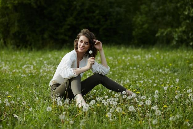 Весенний портрет девушки, сидящей в поле на траве среди цветов одуванчика