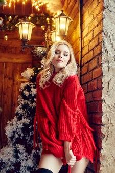 赤いセーターの女性金髪、楽しんで、クリスマスツリーに対してポーズ