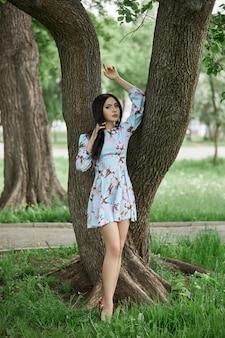 美しい開花木の枝のブルネットの女性。