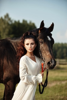 長いドレスを着た女の子が馬のそばに立ち、美しい女性が馬をなでて、秋に野外で手綱を握る