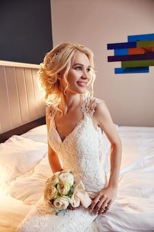 朝の花嫁。花の花束を手に持った白いウェディングドレスを着た女性。