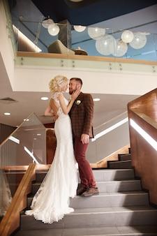 電車と新郎が付いたシックなロングドレスを着た花嫁は大きな階段に立ち、愛のカップルは階段でキスしてお互いを見て