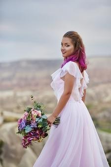 彼女の手に花の美しい花束を持つ女性は、夜明けの夕日の光線で山に立っています