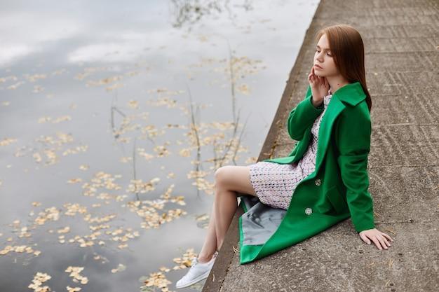 Девушка в зеленом пальто гуляет по набережной озера в пасмурный осенний день.
