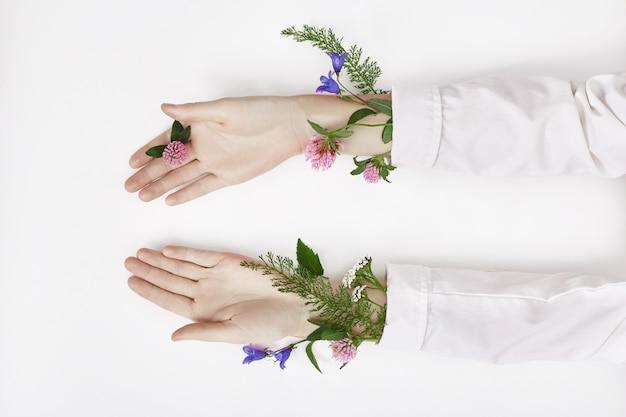 手と春の色の花はテーブルのスキンケアにあります。