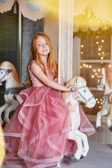 Красивая рыжеволосая девушка с длинными волосами едет на карусели