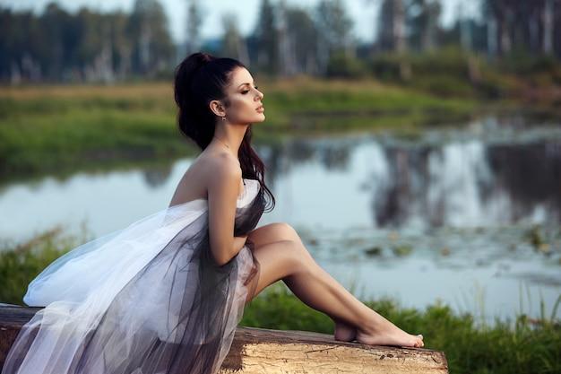 Девушка в длинном платье возле озера сидит на старой лодке
