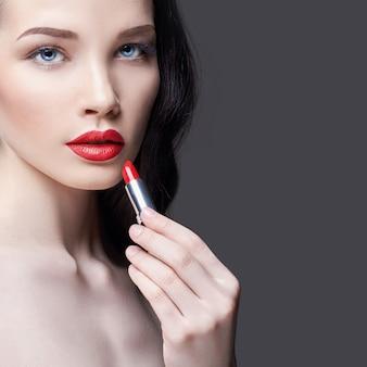 若いブルネットの女性は彼女の唇に真っ赤な口紅を塗る