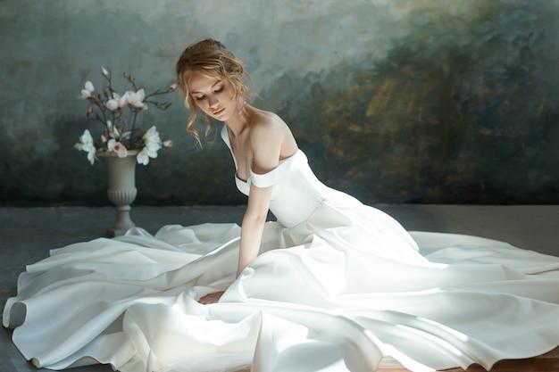 Красивая блондинка девушка сидит на полу в длинном белом платье.