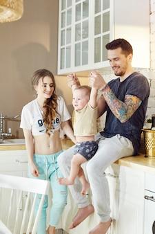 休日の朝に自宅で若い家族。結婚されていたカップルと彼女の腕の中で小さな赤ちゃん。ハグし、楽しんでうれしそうな、幸せな顔