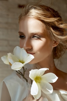 宝石、長い白いドレスを着た女性の肖像画を持つ完璧な花嫁。美しい髪ときれいな繊細な肌。結婚式の髪型金髪の女性。彼女の手に白い花を持つ女性