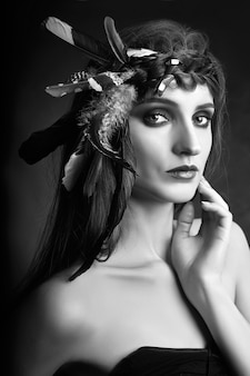 彼女の髪に羽を持つ女性、煙でアメリカインディアンの女性の美しさの肖像画。きれいな肌、コントラストメイクで美しい顔