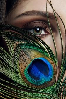 彼女の手に彼女の顔の近くに孔雀の羽を持つ東アラブ女性。美容ファッションメイクアラブの女性、大きな美しい目。美しい滑らかな肌、目の近くの孔雀の羽