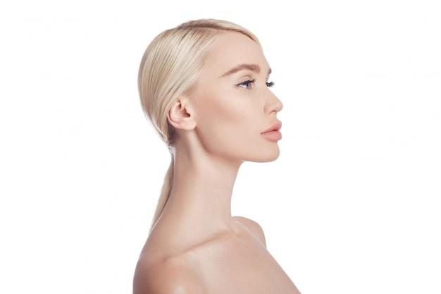 女性の完璧なきれいな肌、しわの化粧品。スキンケアの若返り効果。毛穴のしわをきれいにしません。白い壁に金髪の女性を分離、コピースペース。健康な顔の肌