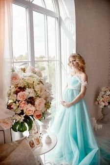 高級ファッション妊娠中のブロンドの女性のウェディングドレス