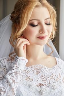 結婚式の日に白いウェディングドレスの美しい花嫁。女性が結婚式の前に婚約者を待っています。彼女の頭にベールを持つ女性