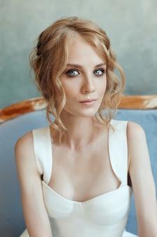 長く白いドレスを着たソファーに座っている美しい細いブロンドの女性。手に花を持つ女性の肖像画。花嫁の完璧な髪型と化粧品
