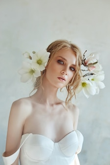 長い白いドレスを着た夕方の太陽の美しい細いブロンド。花を持つ女性の肖像画。花嫁の完璧な髪型と化粧品