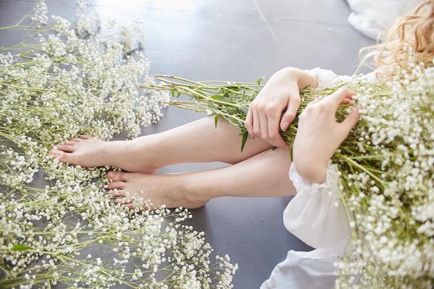 女性は最愛の男に手紙を書き、白い光のドレス、清らかさと無邪気さで自宅のテーブルに座っている。カーリーブロンドのロマンチックな外観、美しい目。テーブルの上の白い野生の花。完璧なボディ