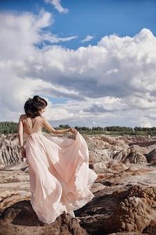 Брюнетка в розовом платье стоит на скале, ветер взъерошивает платье, нежный образ женщины. сказочный горный пейзаж. женщина ветра
