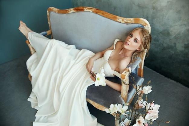 長く白いドレスを着たソファーに座っている美しい細いブロンドの女性。手に花を持つ女性の肖像画。花嫁の完璧な髪型と化粧品、ウェディングドレスの新しいコレクション