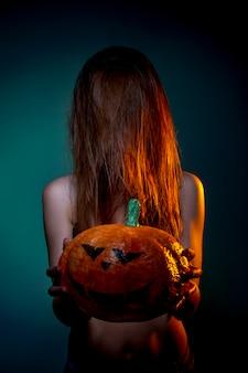 ハロウィーン、彼の手でカボチャと下着の女性。濃い緑の壁の肖像画