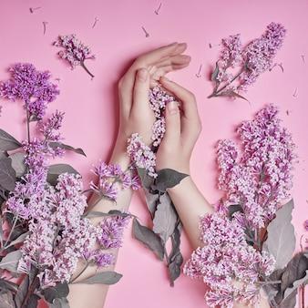 ファッションアートは、自然化粧品の女性、明るいコントラストの化粧、ハンドケアと明るい紫色のライラックの花を手に渡します。テーブルに座っている女性の創造的な美しさの写真