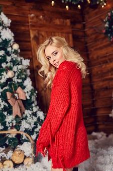 赤いセーターでセクシーなブロンドの女性、楽しんで、クリスマスの装飾でポーズします。村の家の冬とクリスマスツリー。完璧な姿の女性