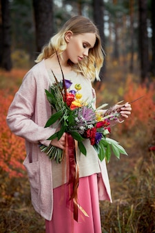 Девушка прогуливается в осеннем лесу. большой красивый букет цветов в руках женщины. девушка стоит в желтой красной траве, осенняя природа