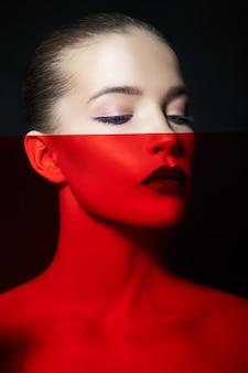 Яркие контрастные красоты макияж портрет женщины в синих и красных тонах. идеально чистая кожа и макияж лица, темная помада на пухлых губах
