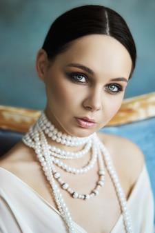 長い白いドレスでソファーに座っていた美しいブルネットの少女。首にジュエリーを持つ女性の肖像画。女性の完璧な髪型と化粧品、軽いドレスの新しいコレクション