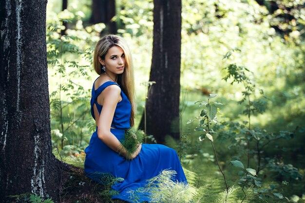森で一人で長い青いドレスの美しい魅力的なブロンド。木と夢に座っている女の子