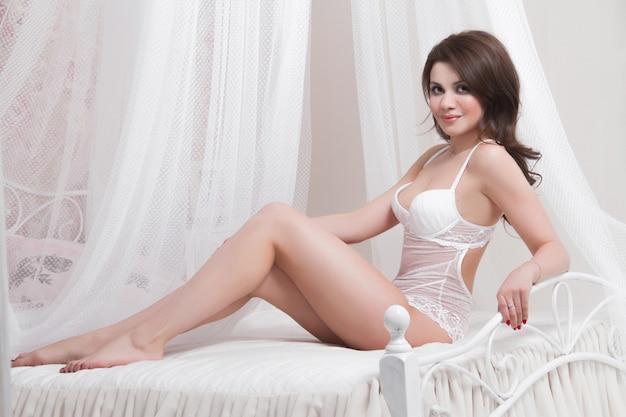 大きな胸を持つ美しいセクシーなブルネットはベッドの上に座っています。寝室で裸のセクシーな女性。家の内部で裸のブルネットのセクシーな肖像画。完璧な裸体のセクシーな女性