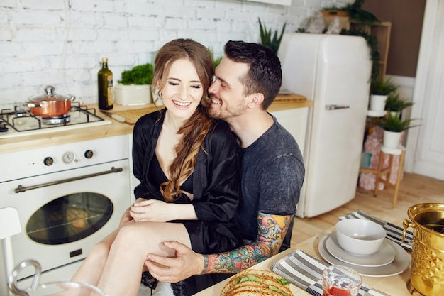 朝の朝食を愛する台所のカップル。男と女がハグし、パンとチーズを切る。愛情のあるカップルの顔に喜びと笑顔