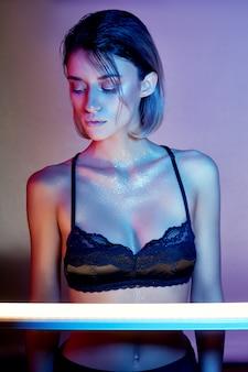 ランジェリーのネオンの光でセクシーな女性。ネオンと少女の顔のまぶしさ。明るいコントラストの光の背景にスパンコールで裸の女性。彼女の顔に美しいメイクとブロンド