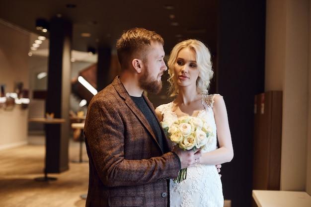 流行に敏感な新郎と新婦、愛と忠誠心。愛のカップルは、結婚式の日に抱擁し、キスします。理想的なカップルは夫と妻になる準備をしています。男と女がお互いを見てクローズアップ