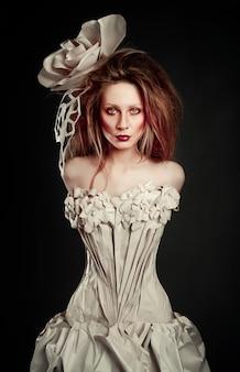 Красивая рыжая девушка в элегантном бумажном платье. чувственное изображение с ярким макияжем. модель красотки