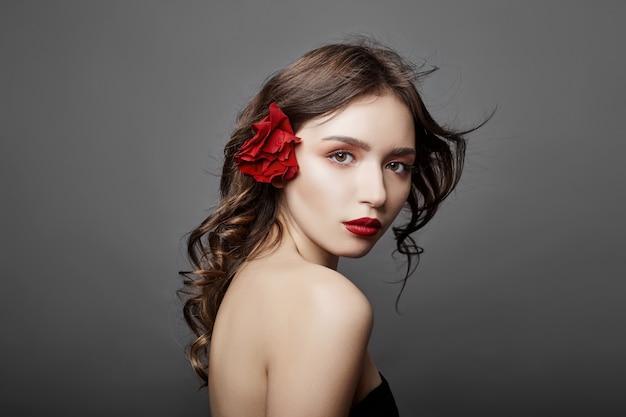 Женщина с большим красным цветком в волосах. темноволосая девушка с красным цветком позирует на сером фоне. большие красивые глаза и естественный макияж. длинные вьющиеся волосы, идеальное лицо